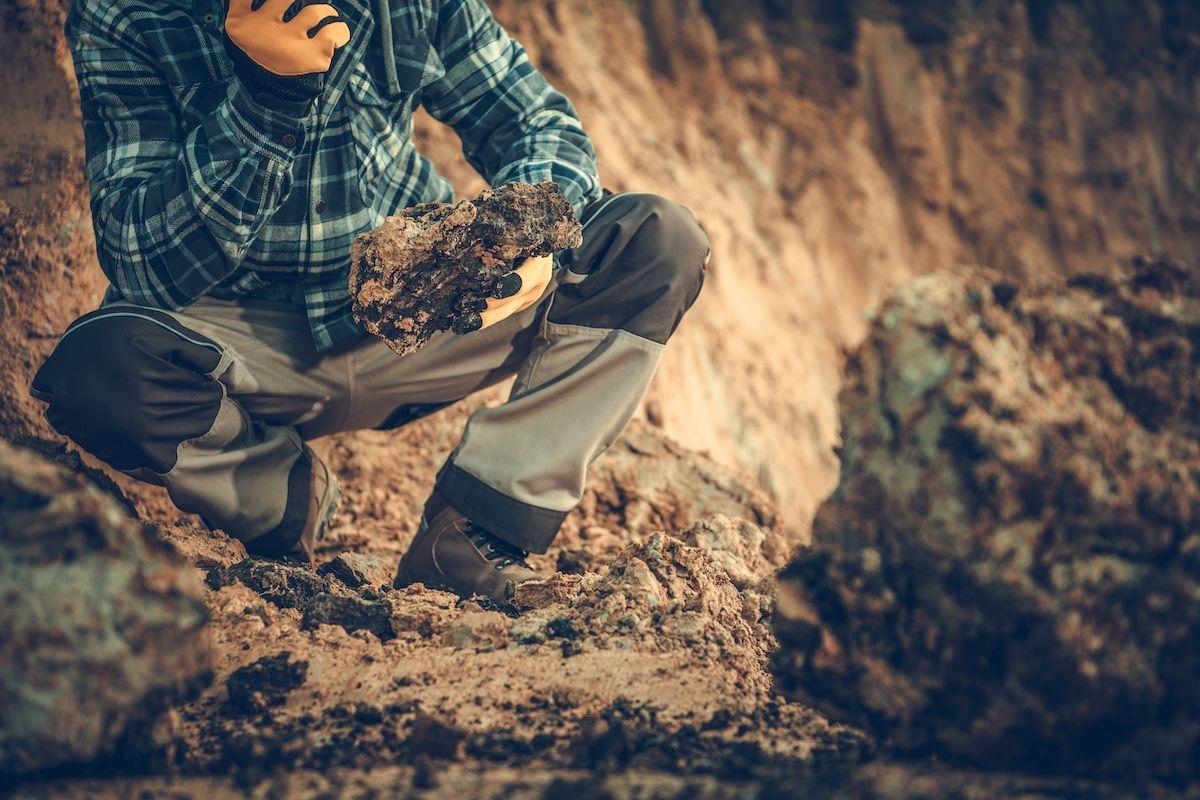 Mann untersucht einen Stein